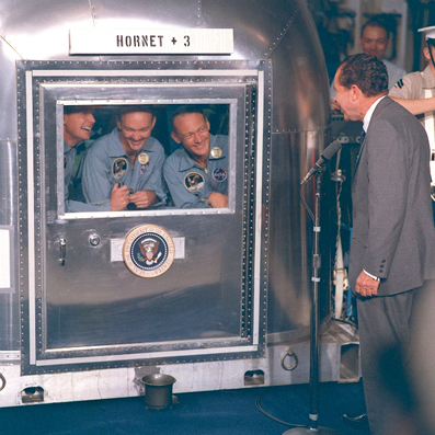 Figure 11. Post-decontamination: The Apollo 11 astronauts safely contained within the screen as they are welcomed back by  President Nixon and the world, 24th July 1969 (Image Courtesy: NASA, Johnson Space Center, Image # S69-21365).