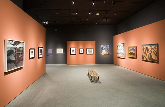 © 2007 Museum Associates/ LACMA View of LACMA installation showing the view towards three modern watercolors by American Indian artists at center on terra cotta colored, built-out wall, with Jonson's Cliff Dwellings at right. The text panel about American Indian watercolor painting hangs at far left next to a John Marin watercolor. Note there two photographs, in black frames, on the left wall next to a Georgia O'Keeffe painting in the foreground at left.