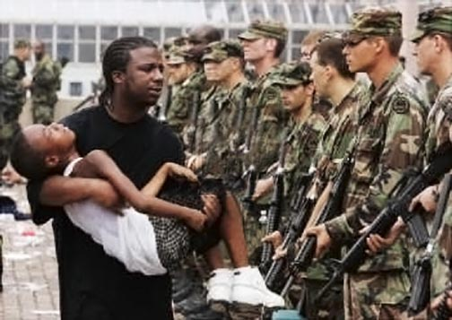 Figure 4. Hurricane Katrina victim carries unconscious boy past fully-armed National Guardsmen on concourse in front of Louisiana Superdome in New Orleans, September 1st. © Michael Appleton, New York Daily News