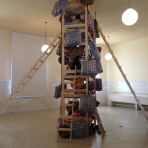 "Fig. 1: Barthélémy Toguo, Climbing Down, 2015, Bunks, hand ladders, multi-colored bags, activated by students from the UNTREF Circus arts program. 500 x 180 x 100 cm. (MUNTREF), Centro de Arte Contemporáneo, located at the site of the former Hotel de Inmigrantes, Buenos Aires, 2015. Photograph courtesy of Caroline ""Olivia"" Wolf."