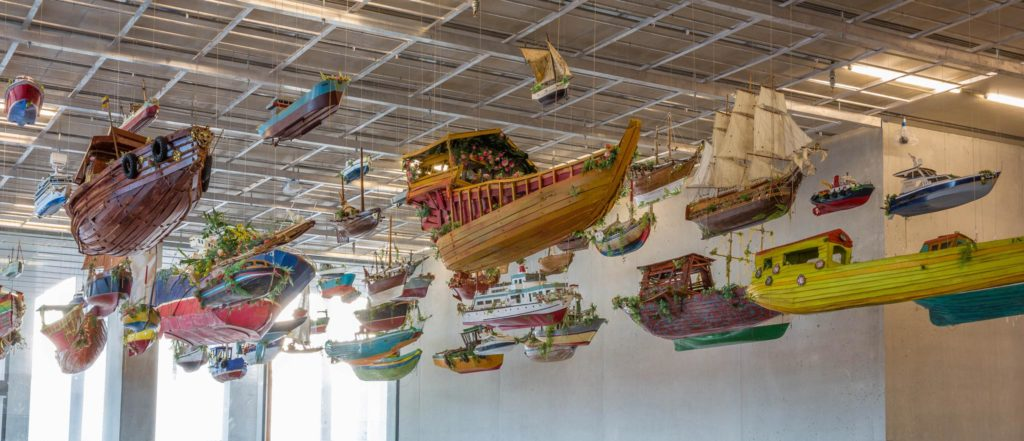 Photo of Hew Locke's installation, For Those in Peril on the Sea. Boats attached to the ceiling, floating.